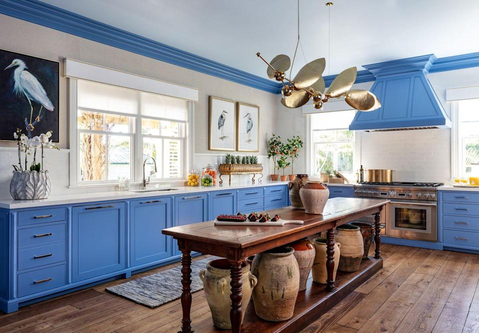 """<p>In this vibrant kitchen at the <a href=""""https://www.veranda.com/decorating-ideas/a30641052/kips-bay-decorator-show-house-palm-beach-2020/"""" rel=""""nofollow noopener"""" target=""""_blank"""" data-ylk=""""slk:Kips Bay Show House"""" class=""""link rapid-noclick-resp"""">Kips Bay Show House</a>, designer <a href=""""http://sarahblankdesignstudio.com/"""" rel=""""nofollow noopener"""" target=""""_blank"""" data-ylk=""""slk:Sarah Blank"""" class=""""link rapid-noclick-resp"""">Sarah Blank</a> furnished the cook space with both functional yet sophisticated pieces. The custom flatweave rug by New Moon Rugs softens the wooden flooring, adding an unexpected layer of texture to the space and a soft landing in front of the sink. A custom fixture by <a href=""""http://www.remains.com/"""" rel=""""nofollow noopener"""" target=""""_blank"""" data-ylk=""""slk:Remains Lighting"""" class=""""link rapid-noclick-resp"""">Remains Lighting</a> hangs above a European tailor's table from <a href=""""https://www.authenticprovence.com/"""" rel=""""nofollow noopener"""" target=""""_blank"""" data-ylk=""""slk:Authentic Provence"""" class=""""link rapid-noclick-resp"""">Authentic Provence</a>. <br></p>"""