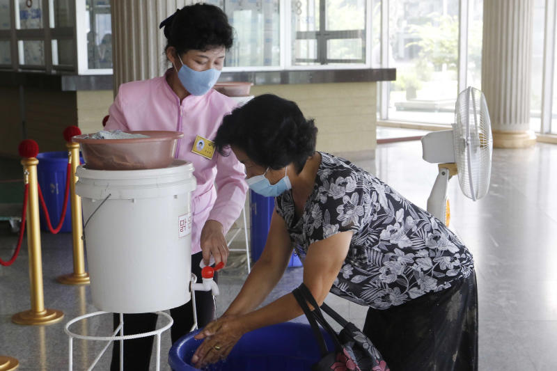 A visitor, right, disinfects her hands to help curb the spread of the coronavirus before entering the Ryugyong Health Complex in Pyongyang, North Korea, Friday, July 31, 2020. (AP Photo/Jon Chol Jin)