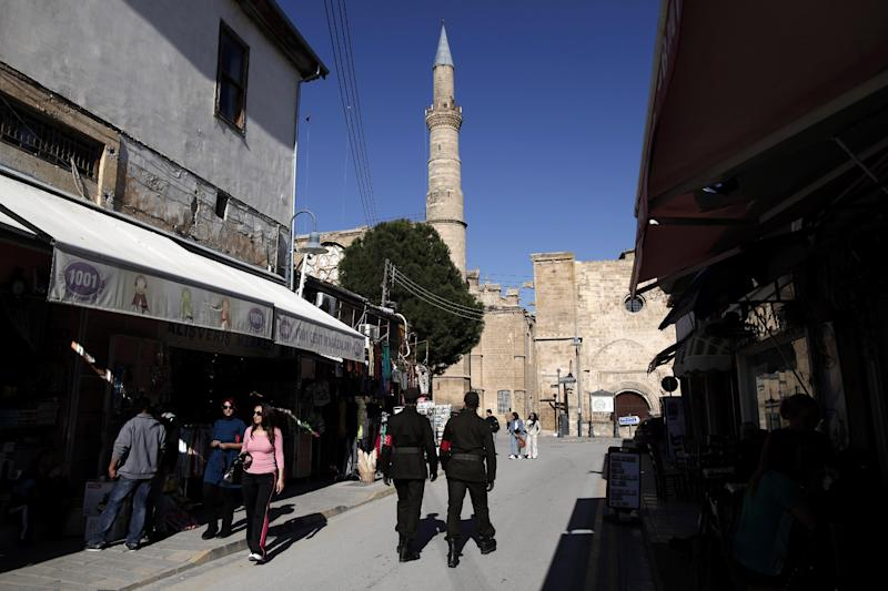 In this photo taken Sunday, March 24, 2013, the minaret of the Selimiye mosque, or Cathedral of St Sophia is seen as soldiers patrol in the Turkish Cypriot part of the divided capital Nicosia. Turkish Cypriots have been watching with fascination - and consternation - as the economy of their long prosperous southern brethren implodes. (AP Photo/Petros Giannakouris)