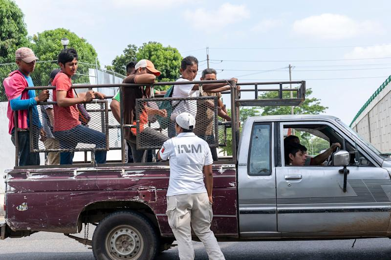 TAPACHULA, Mexico – Mexican National Guard troops stand watch as Mexican immigration authorities question two passengers in a pickup truck at a checkpoint on the northbound highway near Tapachula.