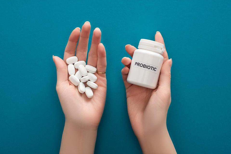 Woman holding white probiotic container and pills in hands.