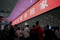 """A red banner hanging at Shenzhen airport arrivals hall read """"Welcome home Meng Wanzhou"""" and a crowd of about 200 supporters gathered waving Chinese flags and banners (AFP/Noel Celis)"""