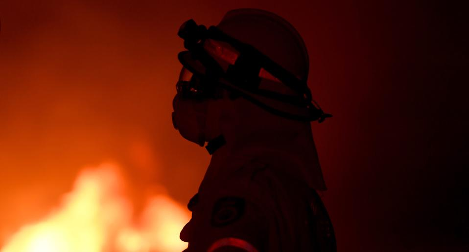A fire fighter observing a NSW bushfire during the Black Summer Bushfires