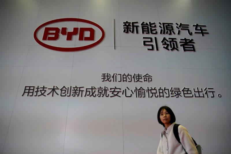 FILE PHOTO: Woman walks past a BYD sign at the second media day for the Shanghai auto show in Shanghai