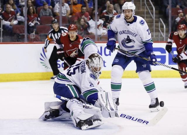 Vancouver Canucks goaltender Jacob Markstrom, left, makes a stick save on a shot by the Arizona Coyotes as Canucks defenseman Alexander Edler (23) looks on during the second period of an NHL hockey team Sunday, March 11, 2018, in Glendale, Ariz. (AP Photo/Ross D. Franklin)