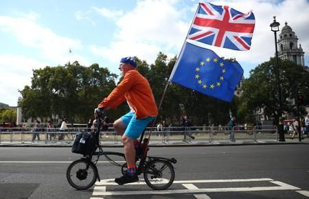 An anti-Brexit protestor rides a bicycle with Union Jack flag and European Union flag attached to it, outside the Houses of the Parliament in London