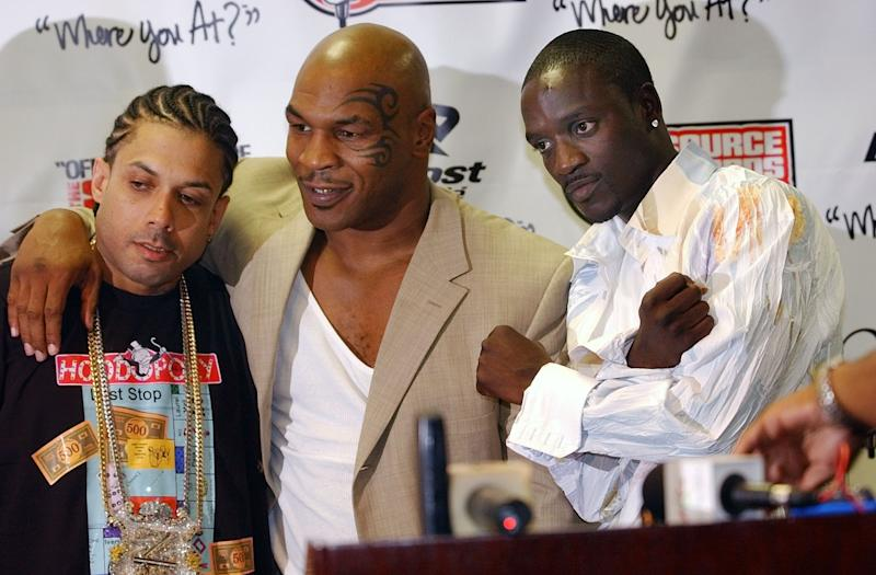 """FILE - In this Oct. 10, 2004 file photo, Ray Benzino, left, from Source Magazine, Mike Tyson and Akon pose for a photo at the Source Hip Hop Awards ceremony in Miami. Benzino says reports were overblown about a massive brawl that included """"Love & Hip Hop: Atlanta"""" cast members during a recent filming of the VH1 reality show. Benzino, whose real name is Raymond Scott, said in an interview Friday, Feb. 8, 2014, that the incident was an """"isolated"""" matter. He said the argument started between his former girlfriend Karli Redd and his fiance, Althea Hart. The incident occurred late Wednesday night during the opening of a new nightclub located in downtown Atlanta, owned by Benzino and Stevie J, the Grammy-winning record producer who also stars on the hit reality show. (AP Photo/J.Pat Carter)"""