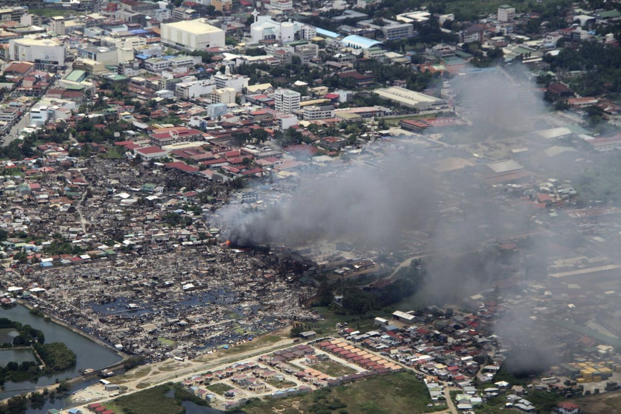 Smoke billows from the site of clashes between government troops and the Muslim rebels of the Moro National Liberation Front (MNLF) in a residential village in Zamboanga city, southern Philippines, in this aerial view taken September 17, 2013, and provided by the Philippine Air Force. Fighting between Philippine forces and Muslim rebels in the southern city has been confined to just two areas and should be over soon, President Benigno Aquino said on Thursday. More than 100 people have been killed and about 112,000 displaced in the fighting with the rebels from a breakaway faction of the MNLF. REUTERS/Philippine Air Force/Handout via Reuters (PHILIPPINES - Tags: POLITICS MILITARY CIVIL UNREST TPX IMAGES OF THE DAY) ATTENTION EDITORS � THIS IMAGE WAS PROVIDED BY A THIRD PARTY. NO SALES. NO ARCHIVES. FOR EDITORIAL USE ONLY. NOT FOR SALE FOR MARKETING OR ADVERTISING CAMPAIGNS. THIS PICTURE IS DISTRIBUTED EXACTLY AS RECEIVED BY REUTERS, AS A SERVICE TO CLIENTS