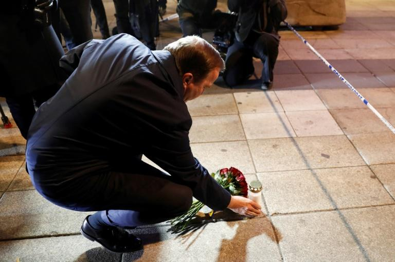 Swedish Prime Minister Stefan Lofven lays flowers and a candle at the scene of a truck attack that killed four people in central Stockholm on April 7, 2017