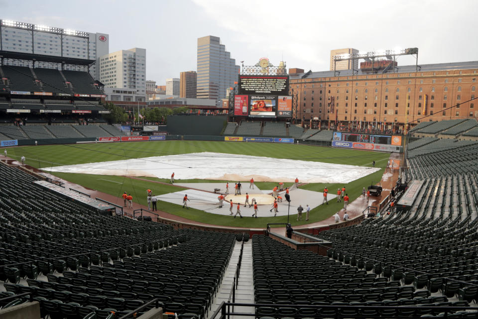 Grounds crew members work on pulling a tarp off the field during a rain delay of a baseball game between the Baltimore Orioles and the New York Yankees, Tuesday, Aug. 6, 2019, in Baltimore. (AP Photo/Julio Cortez)