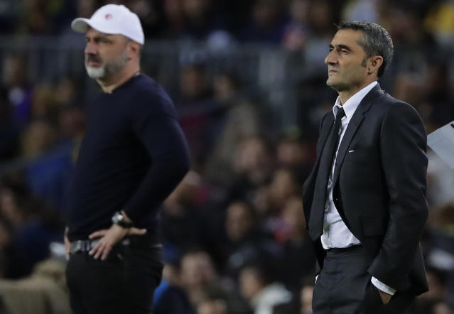 Barcelona's head coach Ernesto Valverde, right, and Slavia's head coach Jindrich Trpisovsky, left, watch their players during a Champions League group F soccer match between Barcelona and Slavia Praha at Camp Nou stadium in Barcelona, Spain, Tuesday, Nov. 5, 2019. (AP Photo/Emilio Morenatti)