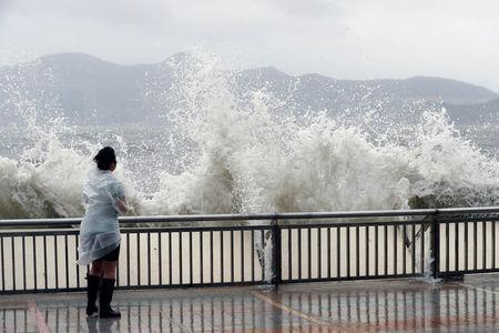 A woman stands beside a big wave on a waterfront Typhoon Hato hitting in Hong Kong, China August 23, 2017. REUTERS/Tyrone Siu