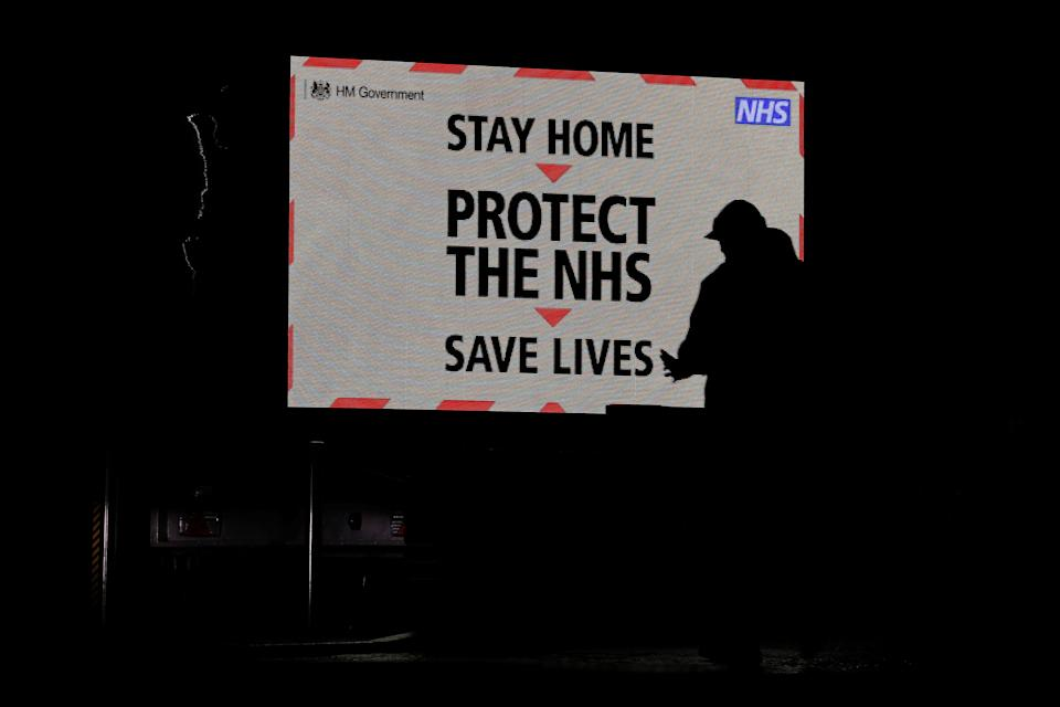 A pedestrian walks past a COVID-19 information display sign outside Aintree University Hospital in Liverpool, northwest England, on January 7, 2021 as the Clap for Carers resumed as 'Clap for Heroes', to show thanks to key workers, including Britain's NHS (National Health Service) workers and other frontline medical staff, for their work during the coronavirus pandemic. - Medical chiefs in England raced to boost treatment capacity on Thursday as a surge in coronavirus cases risked overwhelming hospitals, even as the government stepped up its mass inoculation campaign. (Photo by Lindsey Parnaby / AFP) (Photo by LINDSEY PARNABY/AFP via Getty Images)
