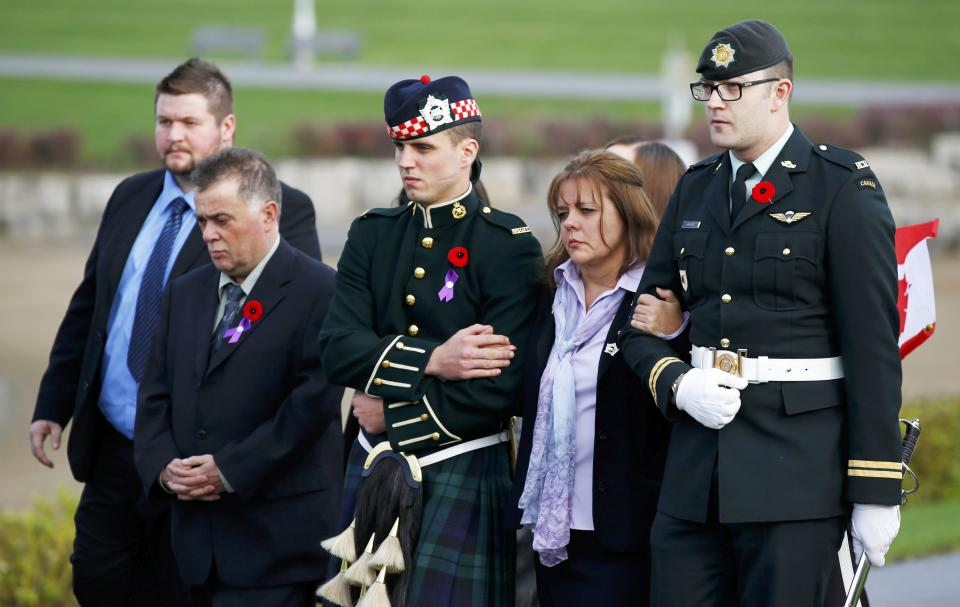 Soldiers escort Kathy Cirillo (2nd R) during the funeral procession for her son Cpl. Nathan Cirillo in Hamilton, Ontario October 28, 2014. Corporal Nathan Cirillo, 24, was one of two soldiers killed in a pair of attacks police said were carried out independently by radical recent converts to Islam at a time when Canada's military is stepping up its involvement in air strikes against Islamic State militants in the Middle East. REUTERS/Mark Blinch (CANADA - Tags: POLITICS MILITARY CRIME LAW OBITUARY)