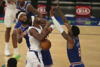 New York Knicks center Mitchell Robinson (23) knocks the ball away from a driving Los Angeles Clippers point guard Reggie Jackson (1) in front of Knicks point guard Elfrid Payton (6) during the first half of an NBA basketball game Sunday, Jan. 31, 2021, in New York. (Brad Penner/Pool Photo via AP)
