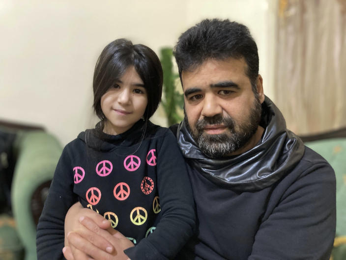 Syrian refugee Mahmoud Mansour, 47, sits with his youngest daughter Sahar, 8, at his rented apartment in Amman, Jordan, Wednesday, Jan. 20, 2021. President Joe Biden has vowed to restore America's place as a world leader in offering sanctuary to the oppressed by raising the cap on the number of refugees allowed in each year. Mansour's family had completed the work to go to the United States when the Trump administration issued its travel ban barring people from Syria indefinitely and suspending the refugee program for 120 days. (AP Photo/Omar Akour)