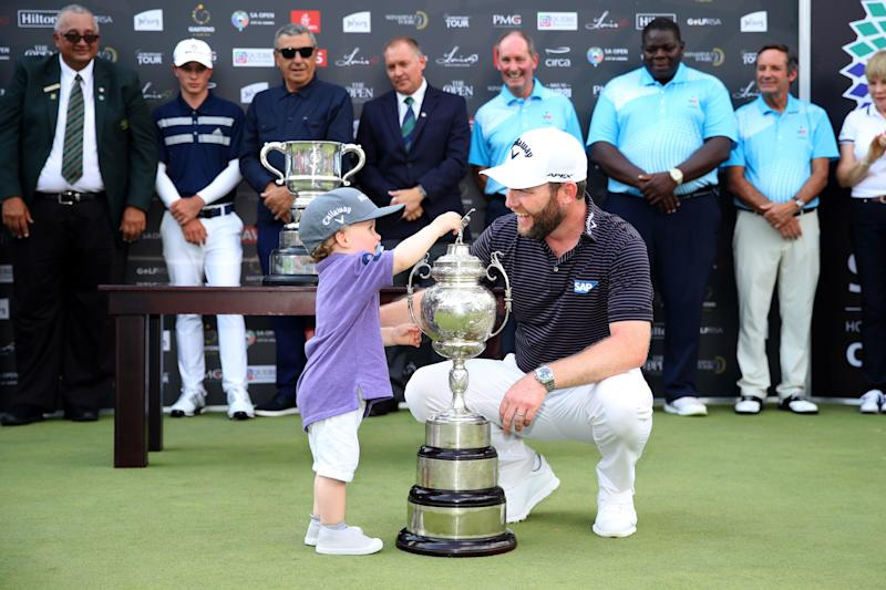 Grace celebrates with his son, Roger, after getting the trophy for winning the 2020 South African Open.