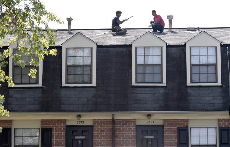 In this Monday, July 29, 2019, photo, men work on a roof at Dutch Village apartments and townhomes, owned by the Kushner Cos., in Baltimore. Jared Kushner's family real estate firm owns thousands of apartments and townhomes in the Baltimore area, and some have been criticized for the same kind of disrepair and neglect that the president has accused local leaders of failing to address. (AP Photo/Steve Ruark)