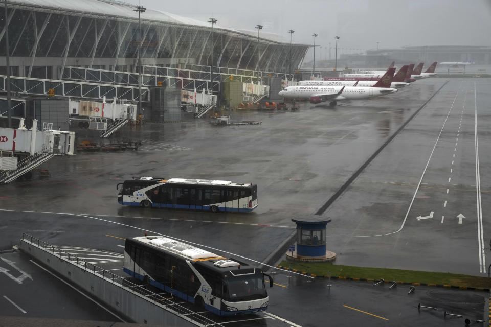 Buses and passenger airplanes are parked on the tarmac after all flights were canceled at Pudong International Airport in Shanghai, China, Sunday, July 25, 2021. Airline flights were canceled in eastern China and cargo ships were ordered out of the area Saturday as Typhoon In-fa churned toward the mainland after dumping rain on Taiwan. (AP Photo/Andy Wong)