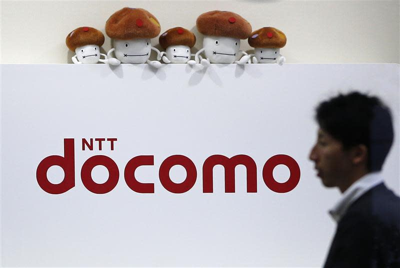 File photo of a man walking past the logo of NTT Docomo at its shop in Tokyo