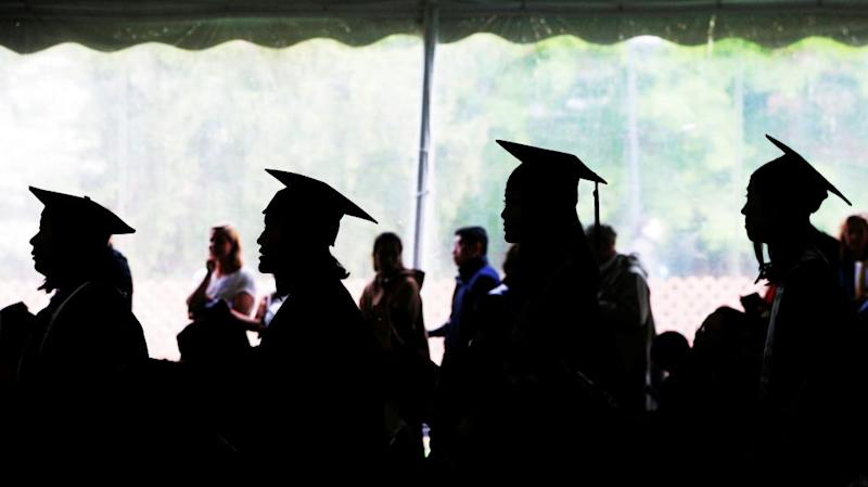 Graduating seniors line up to receive their diplomas during commencement
