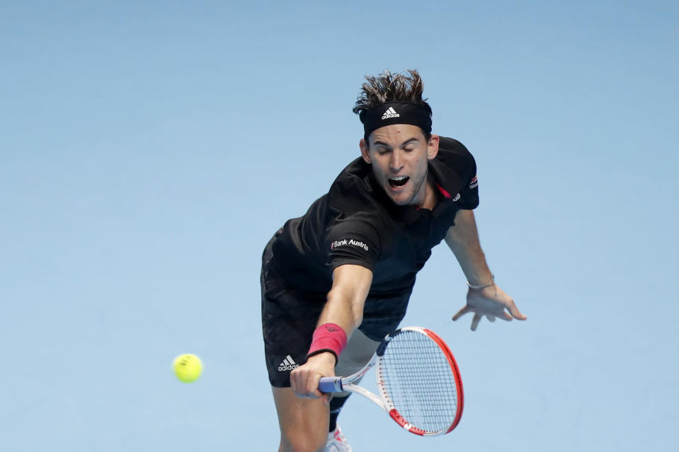 Dominic Thiem of Austria returns the ball to Novak Djokovic of Serbia during their semifinal match at the ATP World Finals tennis tournament at the O2 arena in London, Saturday, Nov. 21, 2020. (AP Photo/Frank Augstein)