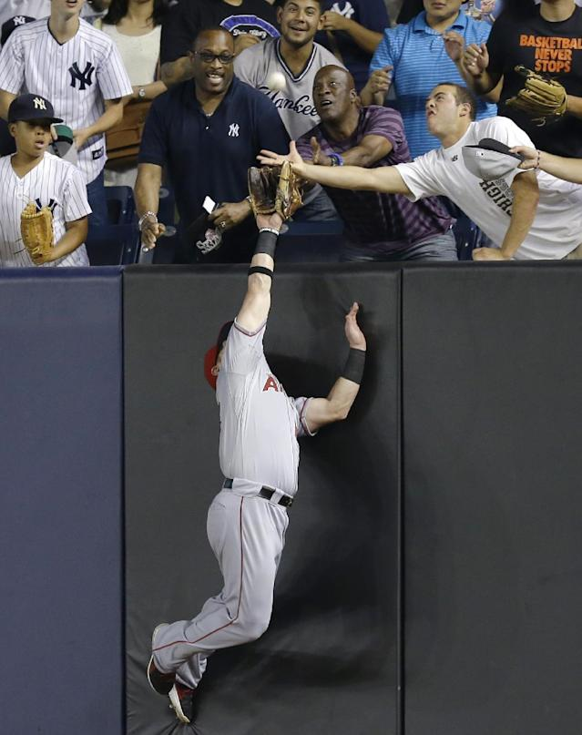 Los Angeles Angels right fielder Kole Calhoun competes with fans for a seventh-inning, three-run home run hit by New York Yankees' Alfonso Soriano in a baseball game, Tuesday, Aug. 13, 2013, in New York. (AP Photo/Kathy Willens)