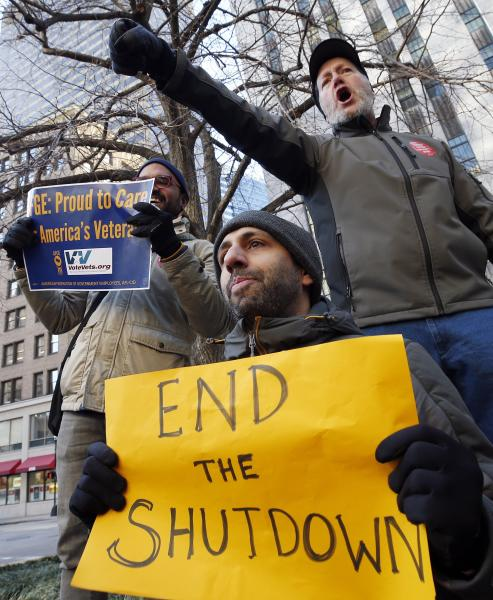 Government workers and their supporters hold signs during a protest in Boston, Friday, Jan.11, 2019. The workers rallied with Democratic U.S. Sen. Ed Markey and other supporters to urge that President Donald Trump put an end to the shutdown so they can get back to work. (AP Photo/Michael Dwyer)