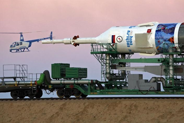 A Russian police helicopter guards the Russia's booster rocket Soyuz-FG with the space capsule Soyuz TMA-11M that will carry new crew to the International Space Station (ISS) as the rocket is transported from hangar to the launch pad at the Russian leased Baikonur cosmodrome, Kazakhstan, Tuesday, Nov. 5, 2013. The rocket is emblazoned with the emblem of the Winter Olympics in Sochi. For the first time, it will also carry an Olympic torch to space as part of the ongoing Olympic torch relay. The torch will be brought back along with the station's current crew. The rocket is scheduled to blast off on Thursday, Nov.7. (AP Photo/Dmitry Lovetsky)