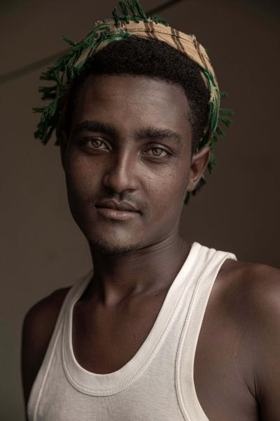 """In this July 21, 2019 photo, 20-year-old Hussein Asfar, a migrant from Ethiopia who was a victim of physical abuse when he landed in Yemen, poses for a portrait in the """"22nd May Soccer Stadium,"""" destroyed by war in Aden, Yemen. Over the summer, the stadium became a temporary refuge for thousands of migrants. At first, security forces used it to house migrants they captured in raids. Other migrants showed up voluntarily, hoping for shelter. The IOM distributed food at the stadium and arranged voluntary repatriation back home for some. The soccer pitch and stands became a field of tents, with clothes lines strung up around them. (AP Photo/Nariman El-Mofty)"""