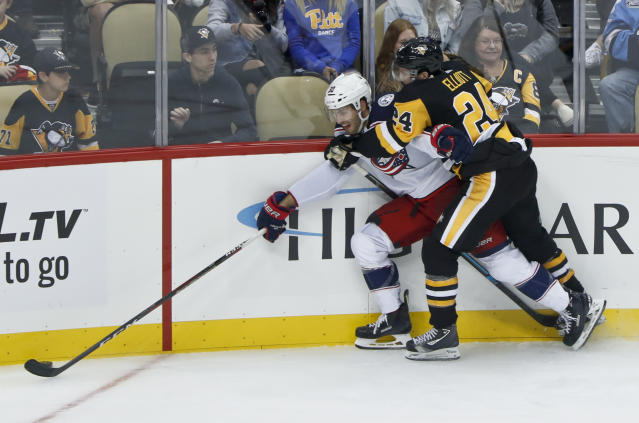 Pittsburgh Penguins' Stefan Elliott (24) grabs Columbus Blue Jackets' Boone Jenner, left, as he checks him along the boards during the third period of an NHL preseason hockey game, Saturday, Sept. 22, 2018, in Pittsburgh. Elliott was penalized 2 minutes for holding on the play. The Penguins won 7-3. (AP Photo/Keith Srakocic)