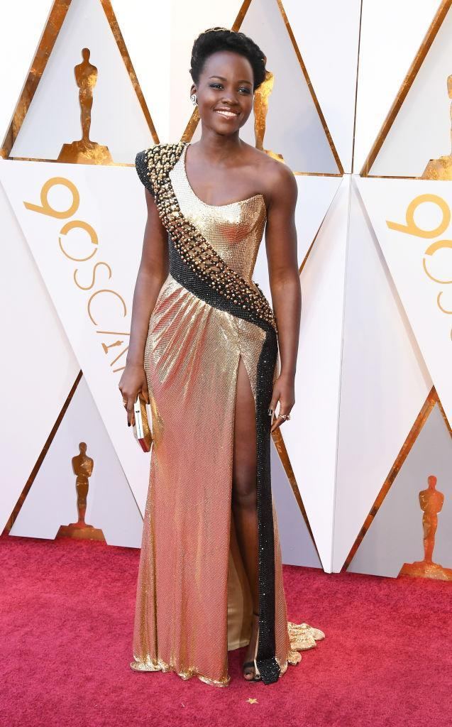 <p><em>Black Panther</em> star Lupita Nyong'o commanded attention in a custom gold dress from Atelier Versace. (Photo: Getty Images) </p>