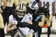 New Orleans Saints quarterback Taysom Hill is tackled by Carolina Panthers free safety Tre Boston during the first half of an NFL football game Sunday, Jan. 3, 2021, in Charlotte, N.C. (AP Photo/Brian Blanco)