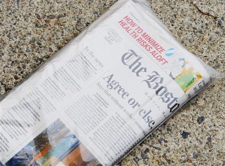 A morning delivery of the Boston Globe newspaper sits on a front porch in Medford