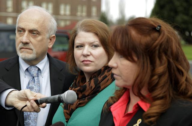Kari Bales, center, stands next to attorney Lance Rosen, left, as they listen as her sister, Stephanie Tandberg, right, reads a statement to reporters Tuesday, Nov. 13, 2012, outside the building housing a military courtroom on Joint Base Lewis McChord in Washington state, where a preliminary hearing ended Tuesday for Kari's husband, U.S. Army Staff Sgt. Robert Bales. Bales is accused of 16 counts of premeditated murder and six counts of attempted murder for a pre-dawn attack on two villages in Kandahar Province in Afghanistan in March of 2012. (AP Photo/Ted S. Warren)