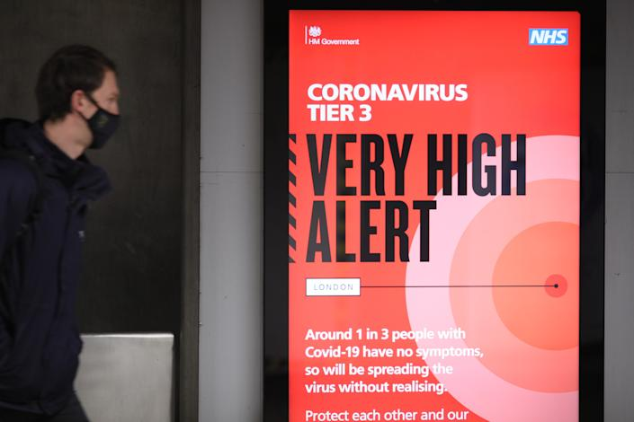 LONDON, Dec. 15, 2020 -- A person walks past a sign at Waterloo Underground Station in London, Britain, on Dec. 15, 2020. London moved into Tier Three, the highest level in England's local coronavirus restriction tier system, from midnight on Wednesday. (Photo by Tim Ireland/Xinhua via Getty) (Xinhua/Tim Ireland via Getty Images)