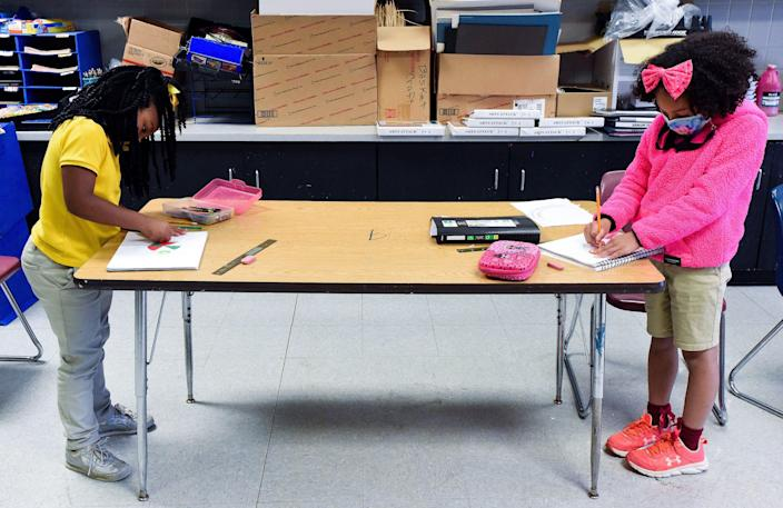 Audrianna Clay, left, and Gabriella DeLoach social distance as they draw during art class at Carver Elementary Arts Magnet School in Montgomery, Ala., on April 20.