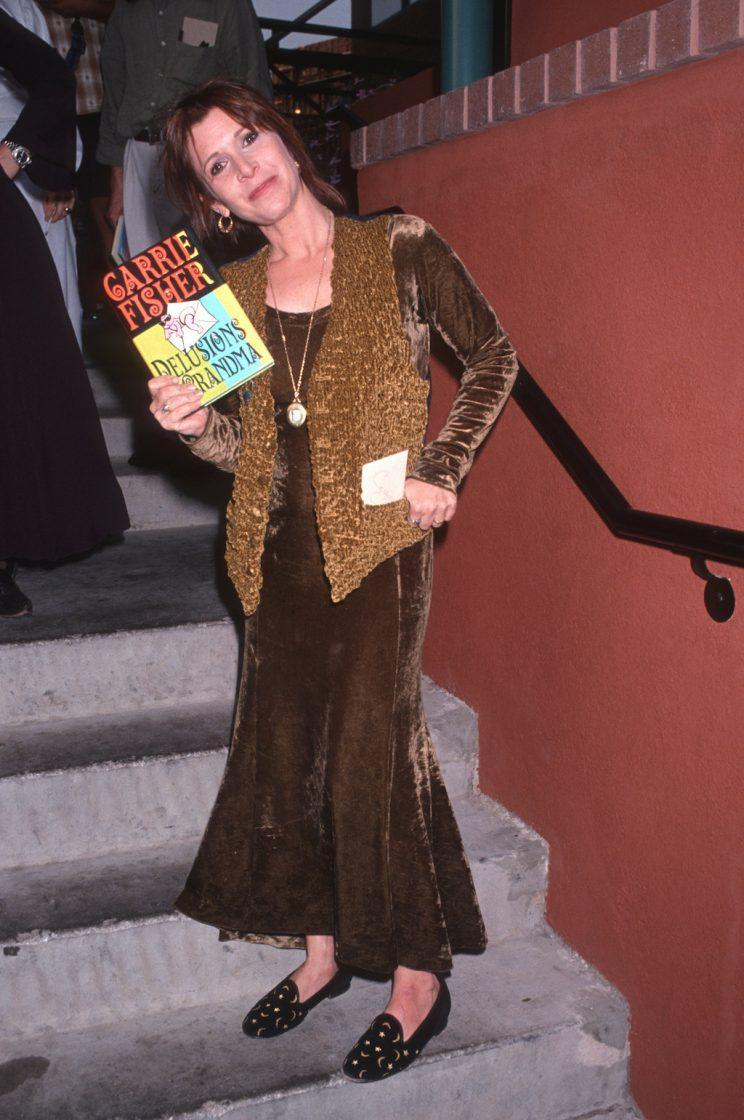 <p>Carrie Fisher holding a copy of her book <em>Delusions of Grandma</em>, published in 1993.</p>