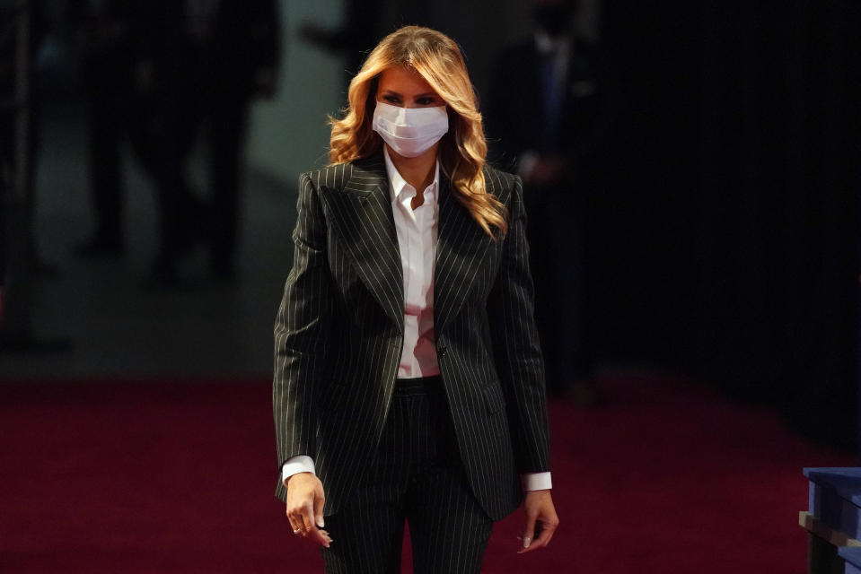 In this Sept. 29, 2020, file photo, first lady Melania Trump, wearing a facemask, walks towards her seat for the during the first presidential debate Tuesday, Sept. 29, 2020, at Case Western University and Cleveland Clinic, in Cleveland, Ohio. President Donald Trump and first lady Melania Trump have tested positive for the coronavirus, the president tweeted early Friday. (AP Photo/Julio Cortez)