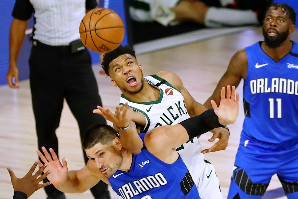 Giannis Antetokounmpo fouls the Magic's Nikola Vucevic late in the Bucks' Game 1 loss on Tuesday. (Photo by Kim Klement-Pool/Getty Images)