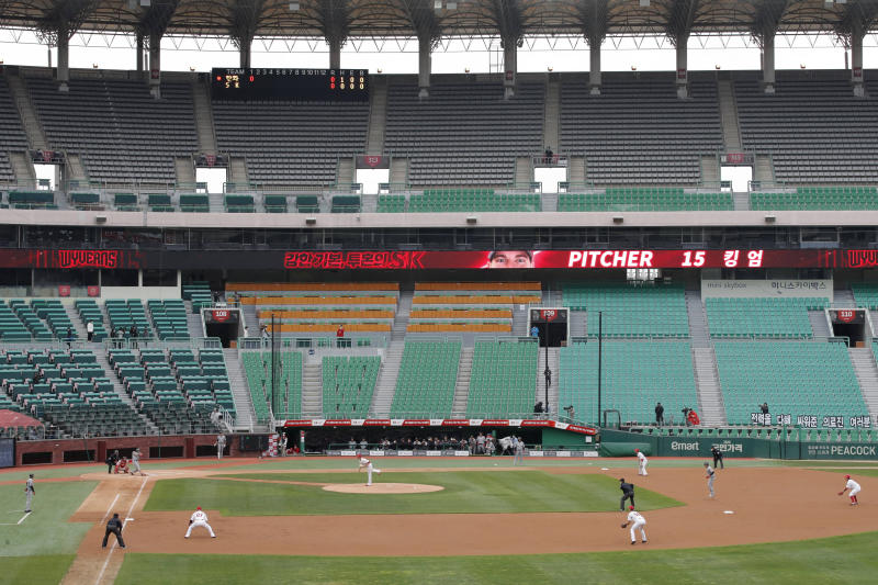 FILE - In this May 5, 2020, file photo, with empty stadium seats, the Hanwha Eagles and the SK Wyverns play during their baseball game in Incheon, South Korea. The baseball league is on. As South Korea significantly relaxes its rigid social distancing rules as a result of waning coronavirus cases, the world is paying close attention to whether it can return to something that resembles normal or face a virus resurgence. (AP Photo/Lee Jin-man, File)