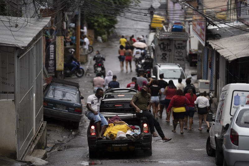 Residents, some wearing masks as a precaution against the spread of the new coronavirus, walk together as they accompany a vehicle transporting the remains of several people who died in an armed confrontation in the Alemao slums complex in Rio de Janeiro, Brazil, Friday, May 15, 2020. According to the civil police, 10 people were found dead during the police operation against alleged drug traffickers. (AP Photo/Leo Correa)