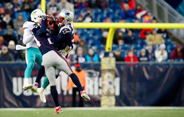 <p>Stephon Gilmore #24 and Duron Harmon #30 of the New England Patriots intercept a pass intended for DeVante Parker #11 of the Miami Dolphins during the fourth quarter of a game at Gillette Stadium on November 26, 2017 in Foxboro, Massachusetts. (Photo by Adam Glanzman/Getty Images) </p>
