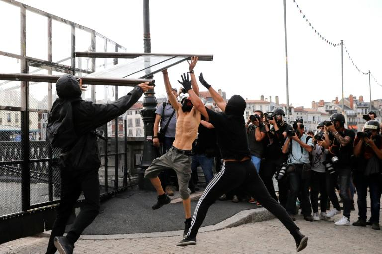 Protesters tear down a part of a barricade put up by French police in Bayonne