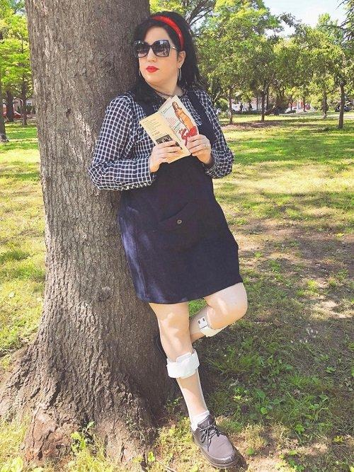 Daffny leaning against a tree. She is wearing a skirt, and her leg braces are visible.