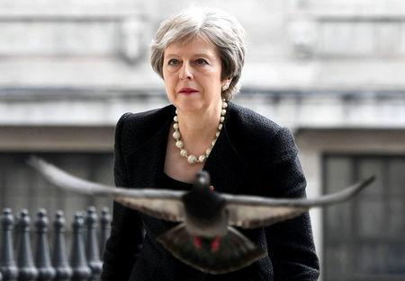 A pigeon flies ahead of Britain's Prime Minister Theresa May as she arrives at a service at St Martin-in-The Fields to mark 25 years since Stephen Lawrence was killed in a racially motivated attack, in London
