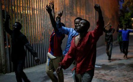 African migrants react as they arrive at the CETI, the short-stay immigrant centre, after crossing the border from Morocco to Spain's North African enclave of Ceuta