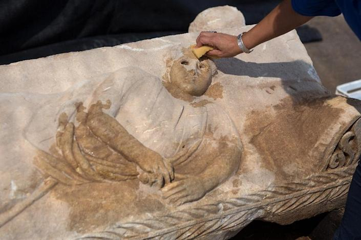 Israel Antiquities Authority southern district director Saar Ganor cleans the lid of a Roman-era sarcophagus adorned with the carving of a young man, at a warehouse in Bet Shemesh on September 3, 2015 (AFP Photo/Menahem Kahana)