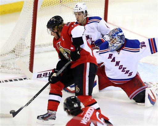 Ottawa Senators' Daniel Alfredsson (11) rushes to the net with the puck as New York Rangers goaltender Henrik Lundqvist and defenseman Michael Del Zotto defend the net during the first period of their NHL hockey game, Thursday, March 28, 2013, in Ottawa, Ontario. (AP Photo/The Canadian Press, Fred Chartrand)