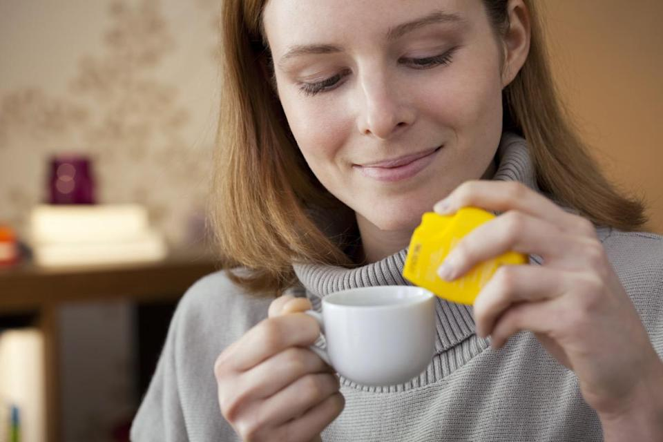 A woman adds artificial sweetener to her coffee cup.